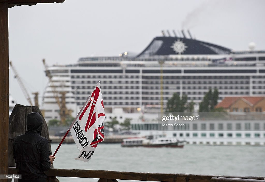 A protestor with a 'No Big Ships' flag looks to a cruise moore at Venice Port during an afternoon of confrontation between Police and protestors during the water blockade of the Venice Tourist Port on June 9, 2013 in Venice, Italy. Three days of protests are being organised by Venetians and environmentalists, who are opposed to cruise ships crossing the St Mark's Basin.