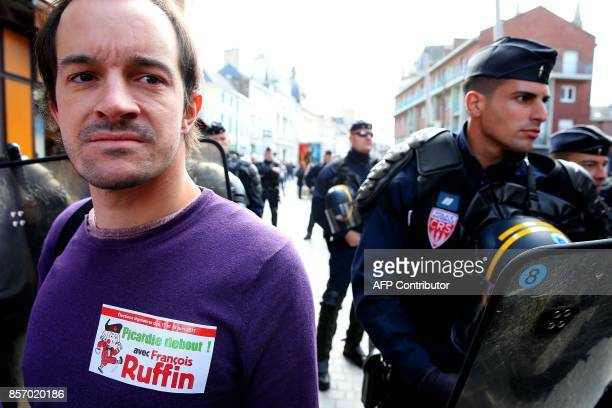 A protestor with a sticker reading 'Picardie stand up with La France Insoumise leftist party's MP Francois Ruffin' next to a riot police during a...