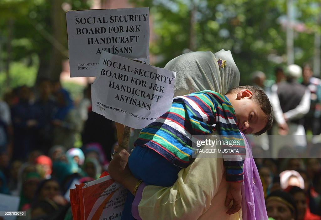 A protestor with a young child on her shoulder carries a placard as she joins other contractual and daily wage employees of the state government during a protest for better pay and job security as they take part in a rally in Srinagar on May 1, 2016. Workers from various labour groups took to the streets on the occasion of the International Labour Day which is observed worldwide. / AFP / TAUSEEF