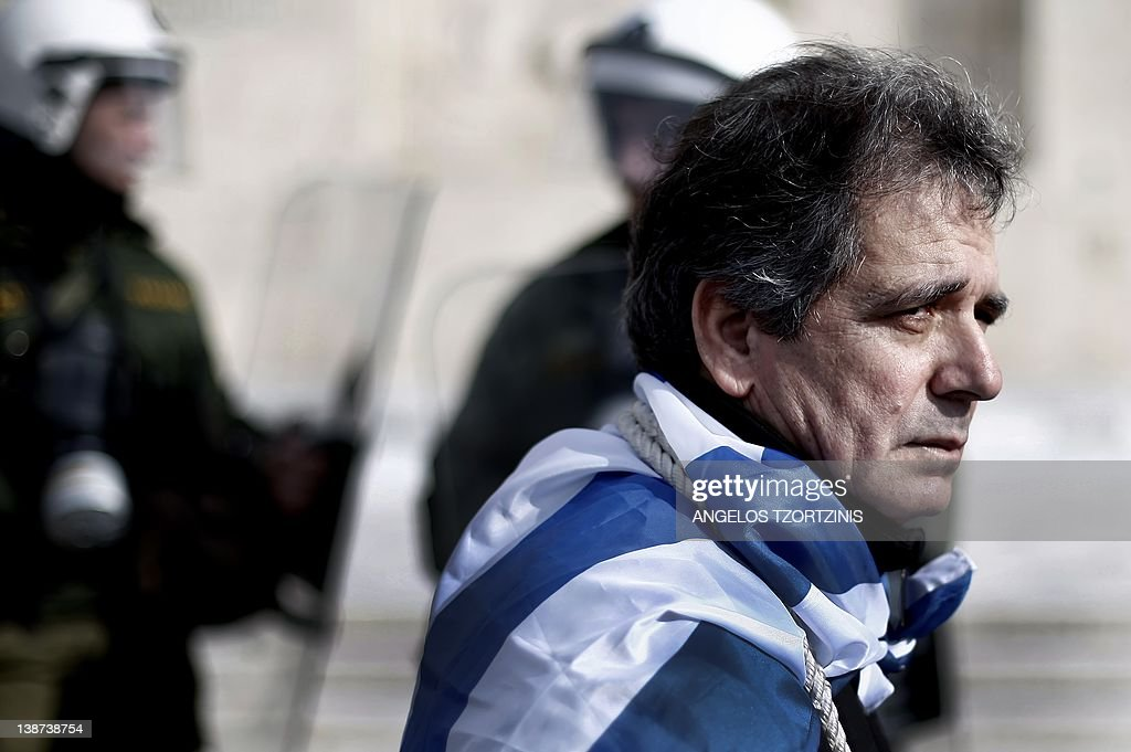 A protestor wrapped in a Greek flag sits in front of police officers during a 48hour antiausterity strike in front of the Greek Parliament on...