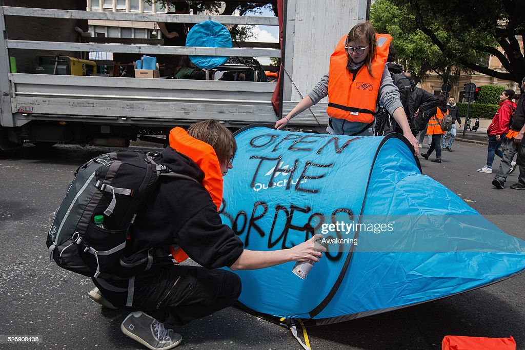 A protestor writes a sign on a tent during May Day protests on May 01, 2016 in Rome, Italy. Police clashed with protestors as hundreds took to the streets to participate in May Day marches and gatherings across Italy, with many demonstrators demanding a solution to the migrant crisis.