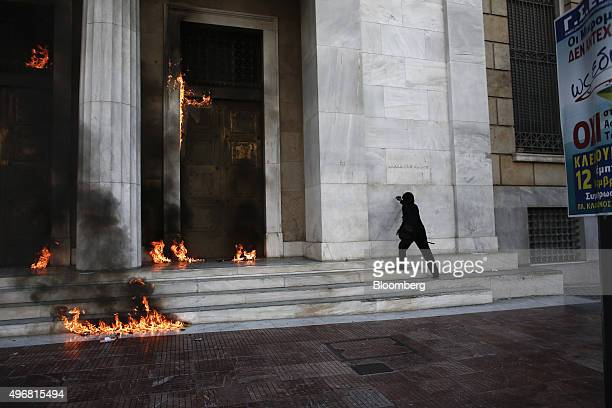 A protestor writes graffiti on the wall of Greece's central bank as the entrance doors burn during a 24 hour general strike in Athens Greece on...