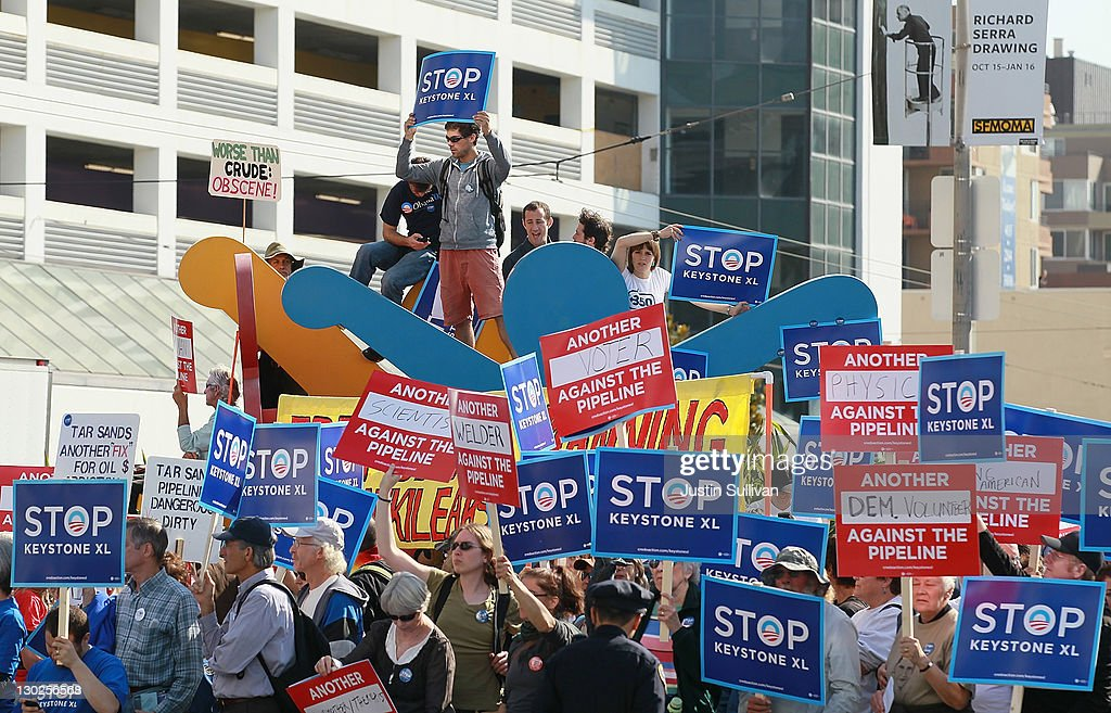 Protestors against the construction of the Keystone XL oil pipeline hold signs and stand on a Keith Haring sculpture as they demonstrate outside of the W Hotel before the arrival of U.S. President Barack Obama on October 25, 2011 in San Francisco, California. Hundreds of protestors from a wide variety of activist groups staged protests outside of the W Hotel where President Obama was holding a $7,500 per person fundraiser.