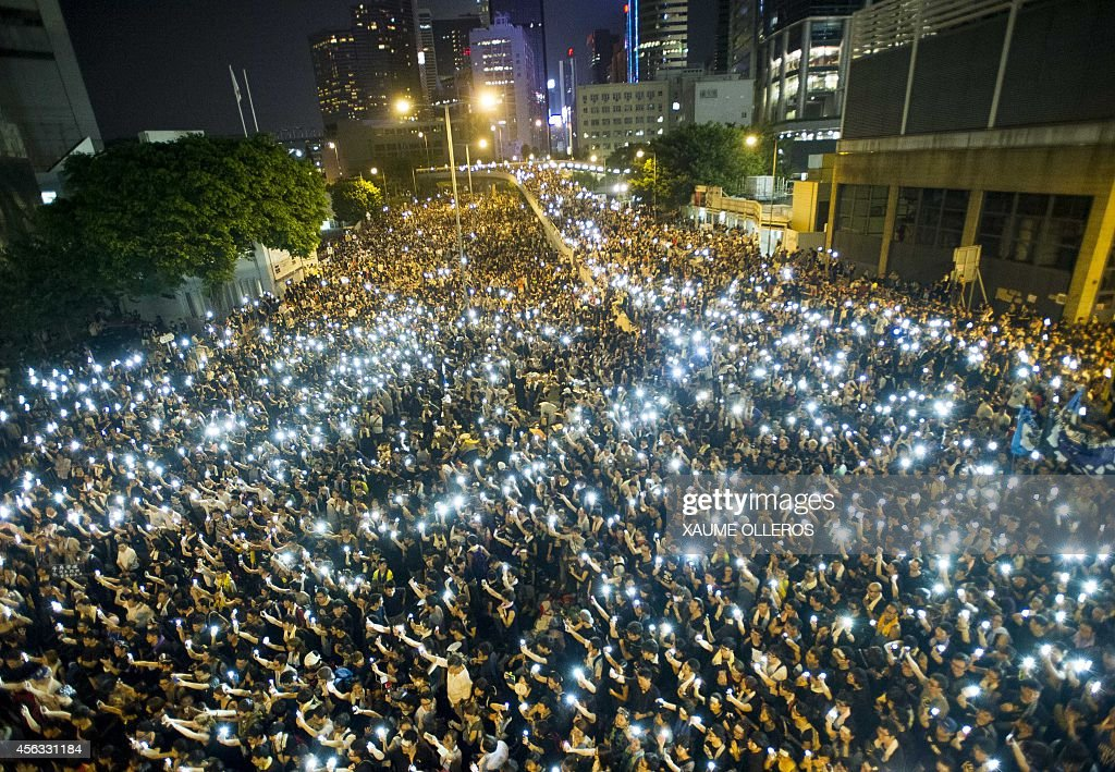 Protestors and student demonstrators hold up their cellphones in a display of solidarity during a protest outside the headquarters of Legislative Council in Hong Kong on September 29, 2014. Hong Kong has been plunged into the worst political crisis since its 1997 handover as pro-democracy activists take over the streets following China's refusal to grant citizens full universal suffrage.