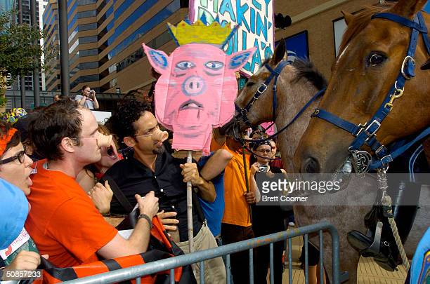 Protestors are pushed behind barricades by police as they protest outside the Halliburton shareholder's meeting May 19 2004 in Houston Texas Nearly...
