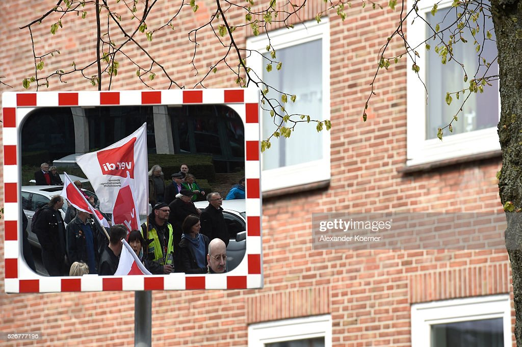 Protestors are reflected in a mirror while participating in the German Confederation of Trade Unions (DGB - Deutscher Gewerkschaftsbund) march on May Day on May 1, 2016 in Hamburg, Germany. Tens of thousands of people across Germany are expected to participate in marches and gatherings by labor unions.