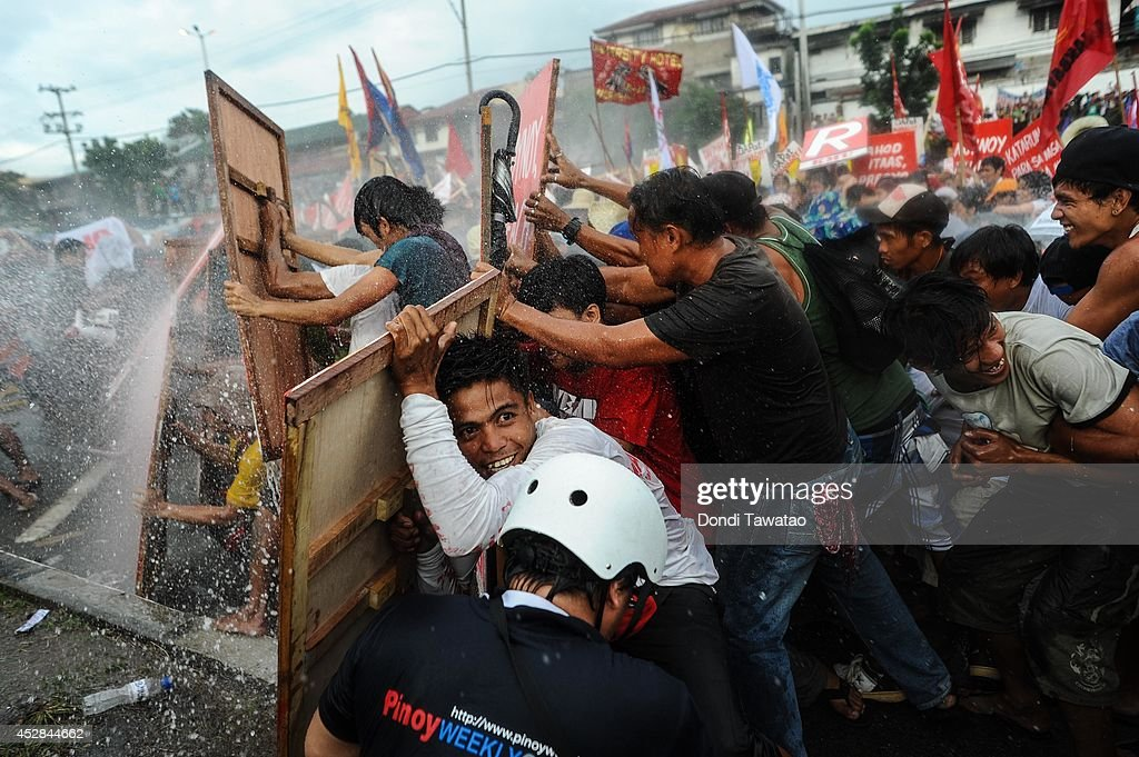 Protestors barricade themselves against water cannon spray during President Benigno Aquino's annual State of the Nation Address on July 28, 2014 in Manila, Philippines. Thousands of government protestors staged a rally to protest the alleged corruption of Aquino involving the Disbursement Allocation Programme, a 145-billion-peso ($3.34-billion) fund to boost public spending but some of the funds went to favored allies in the Lower House of Representatives, reports say.