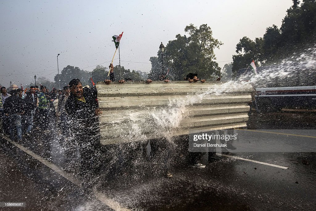 Protestors brace themselves against the spray fired from Police water cannons during a protest against the Indian government's reaction to recent rape incidents in India, in front of India Gate on December 23, 2012 in New Delhi, India. The gang rape of a 23-year-old paramedical student in a moving bus on December 16, in Delhi, has led people to react openly against the government's current rape laws. Over a thousand protesters gathered in front of Delhi to protest against lax laws and the government's handling of recent rape cases all over India.