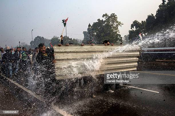 Protestors brace themselves against the spray fired from Police water cannons during a protest against the Indian government's reaction to recent...