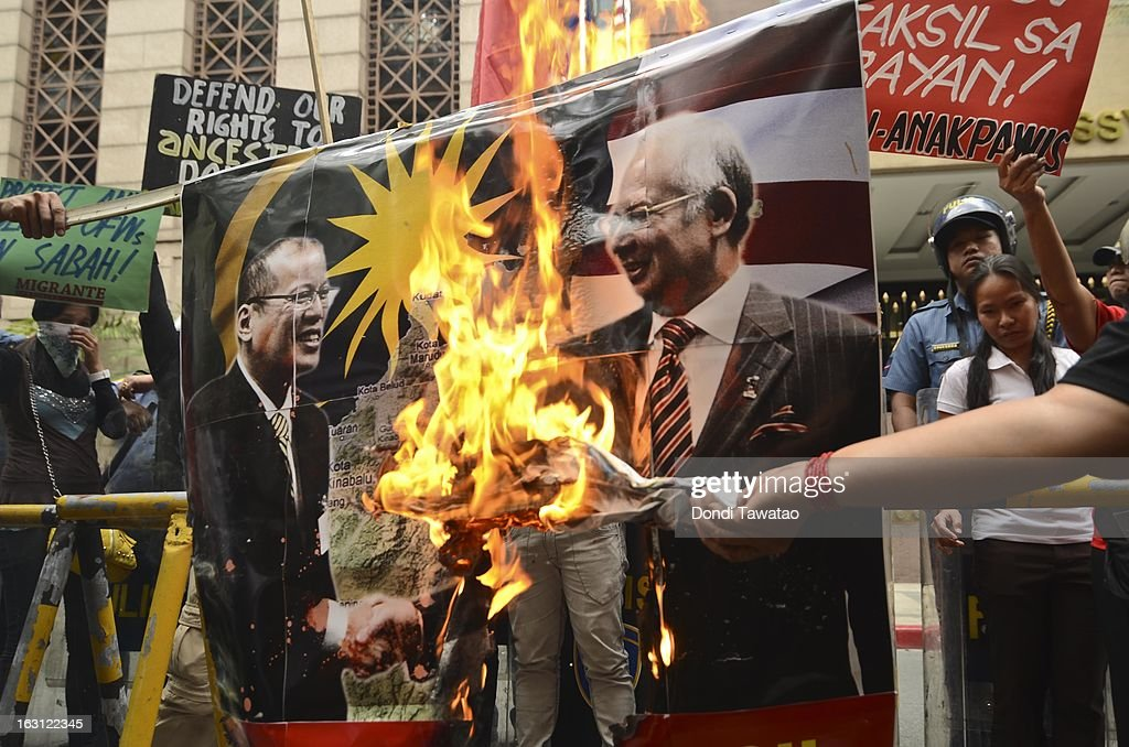 Protestors burn an image of Philippine President Benigno Aquino and Malaysian Prime Minister Najib Razak during a rally outside the Malaysian embassy in the financial district of Makati on March 5, 2013 in Manila, Philippines. The protestors demand an end to hostilities that have so far claimed the lives of 17 followers of self-proclaimed Sultan of Sulu Jamalul Kiram III and 8 Malaysian security forces in the villages of Lahad Datu and Semporna in Sabah. Around 200 armed followers of Kiram in the restive southern provinces of Sulu and Tawi Tawi in Mindanao crossed over to neighboring Sabah last February 12 to lay claim to territory as ancestral land triggering clashes with Malaysian security forces. Philippine diplomatic officials confirmed Tuesday that security forces in Malaysia have conducted airstrikes and ground assault on the 'royal army' of the Sultanate of Sulu in Lahad Datu, Sabah.