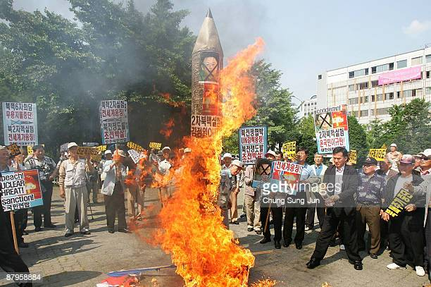 Protestors burn portraits of North Korean leader Kim JongIl and a mock up of a North Korean missile during a protest against North Korea on April 8...