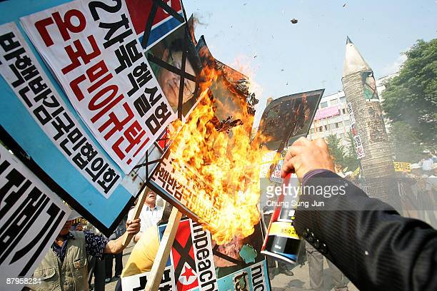 Protestors burn portraits of North Korean leader Kim JongIl during a protest against North Korea on May 25 2009 in Seoul South Korea Protests in...