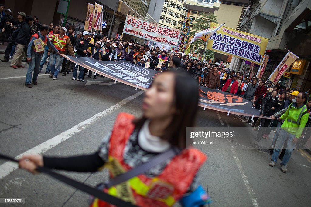 Protestors carry a banner during a rally urging Hong Kong's Chief Executive Leung Chun-ying to step down at Causeway Bay on January 1, 2013 in Hong Kong, Hong Kong. Tens of thousands of protesters took to the streets of Hong Kong calling for the city's embattled leader to quit and demanding greater democracy 15 years after it returned to Chinese rule.
