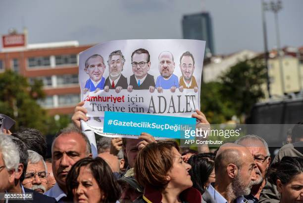 Protestors carry a banner of the jailed journalists during a demonstration in front of Istanbul's court house on September 25 2017 during a hearing...