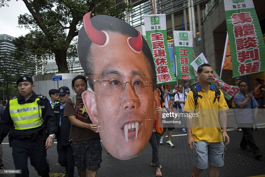 Protestors carry an effigy of Victor Li, deputy chairman of Cheung Kong (Holdings) Ltd., as they walk by the Cheung Kong Center during a Labor Day march in Hong Kong, China, on Wednesday, May 1, 2013. Thousands of Hong Kong residents took to the streets today for Labor Day marches to petition for better labor conditions and in support of strike action by workers at docks operated by Li. Photographer: Jerome Favre/Bloomberg via Getty Images