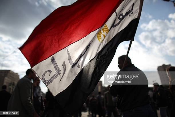 Protestors carry an Egyptian flag through Tahrir Square on January 31 2011 in Cairo Egypt As President Mubarak struggles to regain control after six...