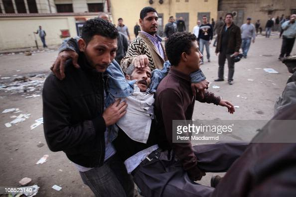 Protestors carry an injured man during clashes with riot police near Tahrir Square on January 29 2011 in Cairo Egypt Tens of thousands of...