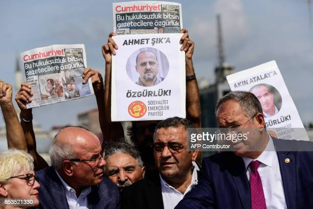 Protestors carry copies of the Cumhuriyet daily and placards of the accused during a demonstration in front of Istanbul's court house on September 25...