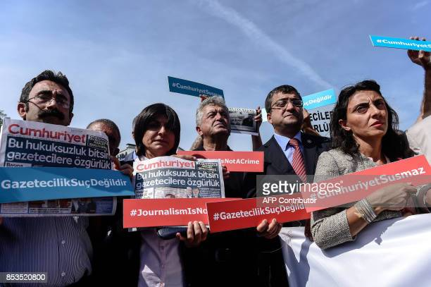 Protestors carry signs and copies of the Cumhuriyet daily during a demonstration in front of Istanbul's court house on September 25 2017 during a...