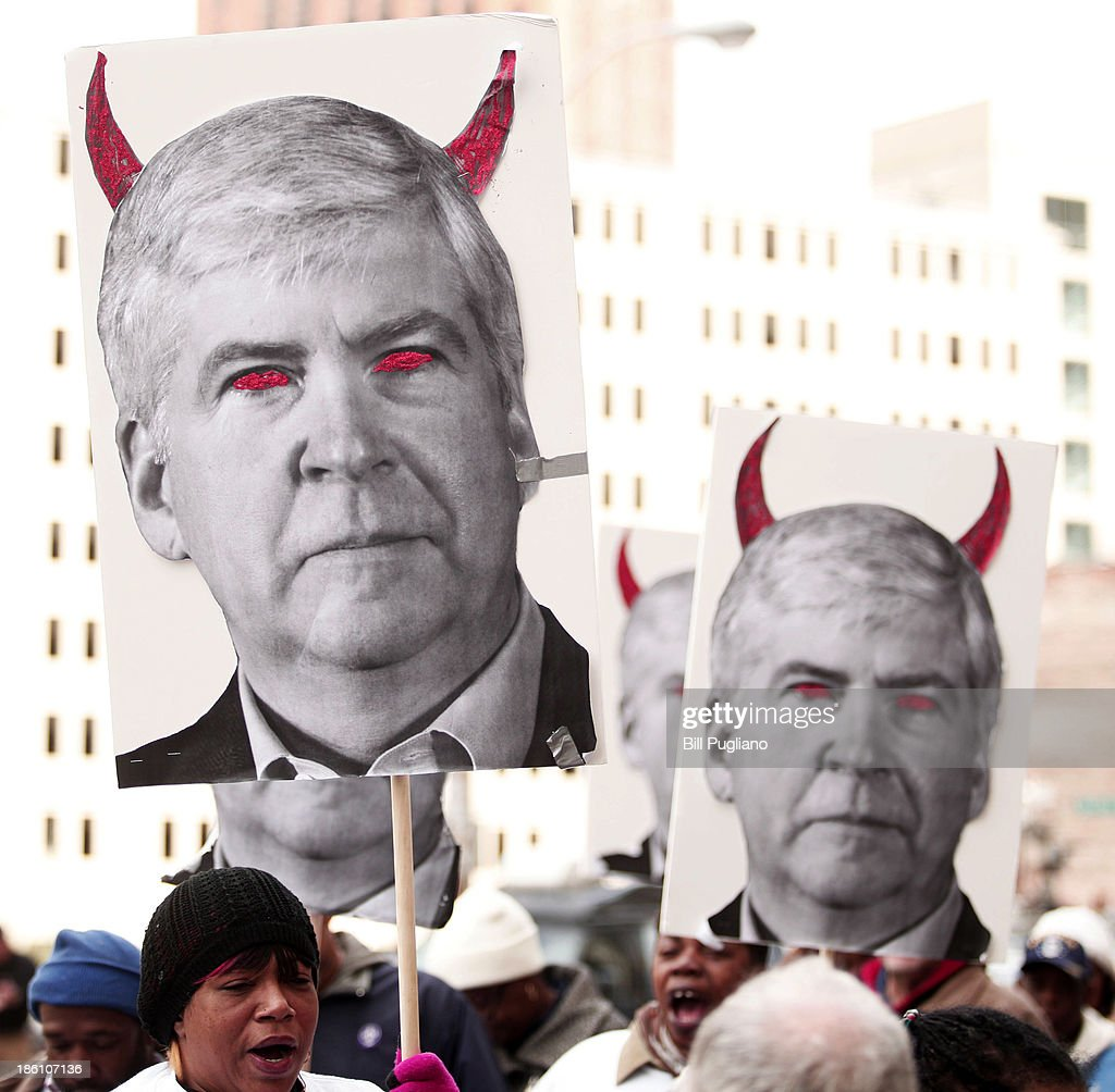 Protestors carry signs that depicts Michigan Gov. Rick Snyder as a devil during a rally in front of the U.S. Courthouse in Detroit where Detroit's bankruptcy eligibility trial is taking place October 28, 2013 in Detroit, Michigan. Michigan Gov. Rick Snyder is expected to testify today at the trial. A federal judge will decide if the City of Detroit is eligible to be in bankruptcy court.