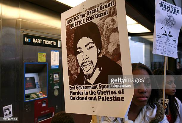 Protestors carry signs with a picture of slain twenty two yearold Oscar Grant III during a demonstration at the Fruitvale BART station January 7 2009...