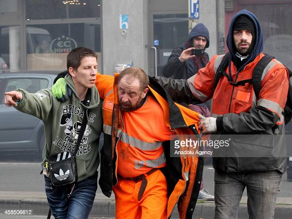 Protestors carry their friends following the police intervention after they burn a police motorbike in Brussels on November 6 2014 Belgians protest...