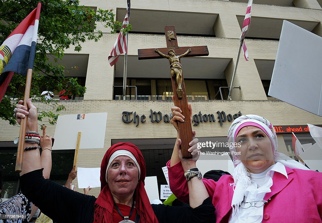Protestors carrying a crucifix and an Egyptian flag join with a large crowd gathered in front of the Washington Post building to protest coverage of Egypt and against the Muslim Brotherhood and its' treatment of Christians on August, 22, 2013 in Washington, DC.