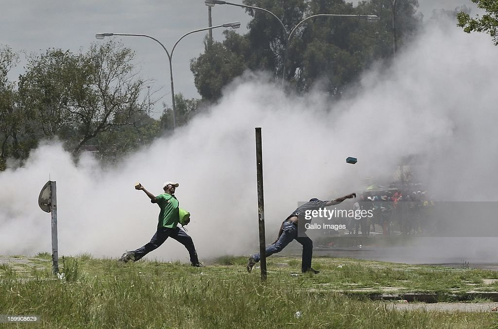 Protestors cast stones at vehicles on January 22, 2013, in Sasolburg, South Africa. The announcement of government's intention to merge municipalities in the Free State sparked outrage in Zamdela township residents.
