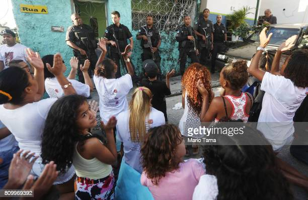 Protestors chant in front of police officers following the funeral of Vanessa dos Santos who was shot in the head and killed in the doorway of her...