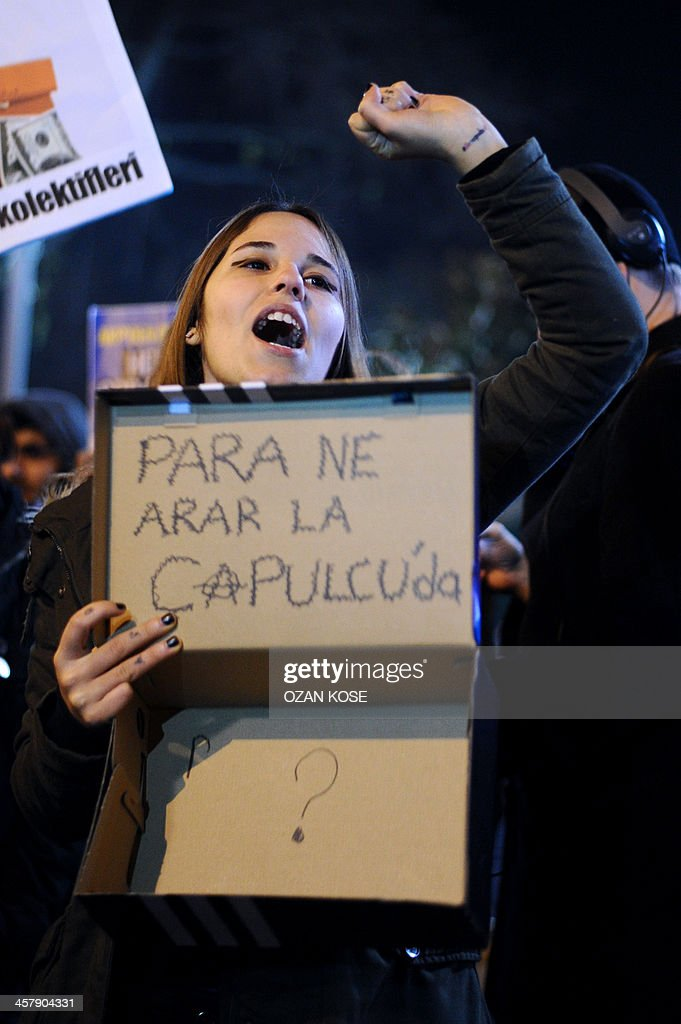 A protestors chants slogans and holds a shoebox with text reading 'We have no money ?' as she marches to the entrance of a Halkbank bank branch in the Besiktas district of Istanbul on December 19, 2013. About 100 protestors chanted anti-goverment slogans as they protested corruption during a demonstration rally. Turkish police had detained more than 20 people including the sons of three cabinet ministers and several high-profile businessmen on December 17 in a probe into alleged bribery and corruption, local media reported. AFP PHOTO / OZAN KOSE
