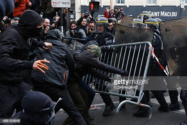 Protestors clash with riot police clash during a rally against global warming on November 29 2015 in Paris a day ahead of the start of UN conference...