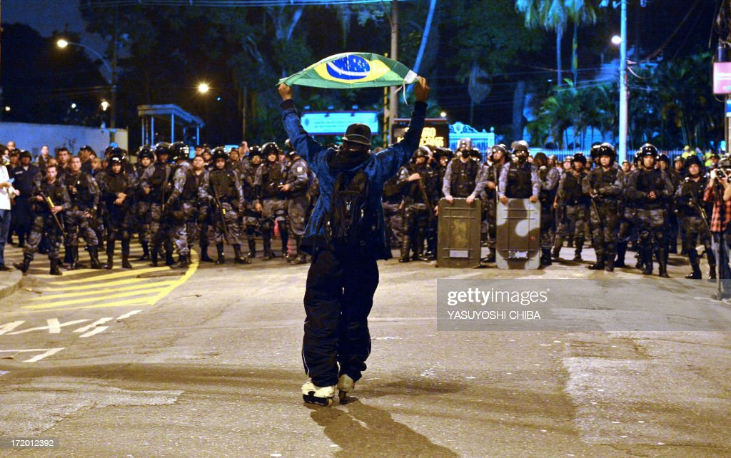 Protestors clash with riot squad officers on a street near Maracana stadium in Rio de Janeiro, Brazil on June 30, 2013, a few hours before the final of the FIFA Confederations Cup football tournament between Brazil and Spain. More than 11,000 police and troops were mobilised in the city to guarantee security for 78,000 fans at the venue as the curtain falls on a competition that has been beset by social unrest with more than 1.5 million people taking to the streets across the giant nation in the past two weeks. AFP PHOTO / YASUYOSHI CHIBA