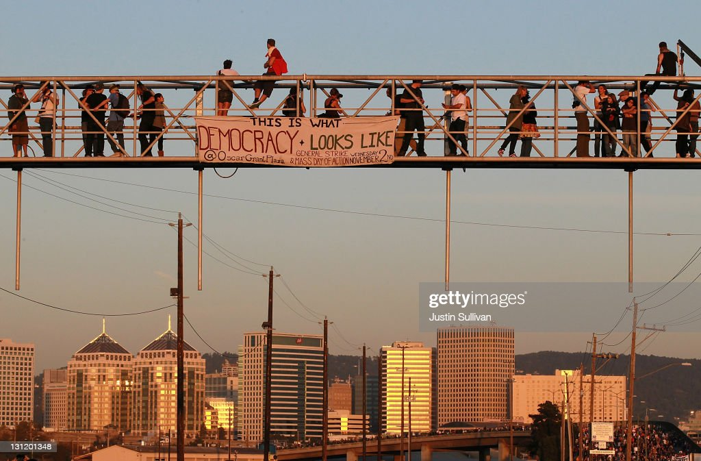 Protestors climb on a railroad crossing at the Port of Oakland during Occupy Oakland's general strike on November 2, 2011 in Oakland, California. Tens of thousands of protestors have tmarched to the Port of Oakland for a general strike organized by Occupy Oakland. Port operations shut down for the evening.