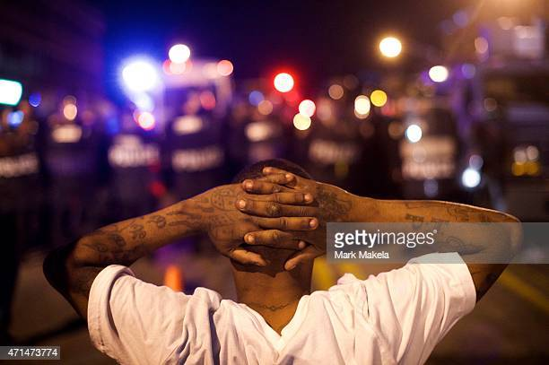 Protestors defy curfew and taunt police officers the night after citywide riots over the death of Freddie Gray on April 28 2015 in Baltimore Maryland...