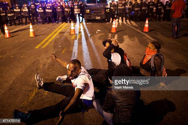 Protestors defy curfew in front of police officers the night after citywide riots over the death of Freddie Gray on April 28 2015 in Baltimore...