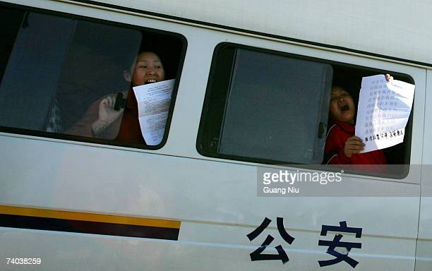 Protestors demonstrate from the windows of a police van in Tiananmen Square on May 1 2007 in Beijing China 50 people were removed after demonstrating...