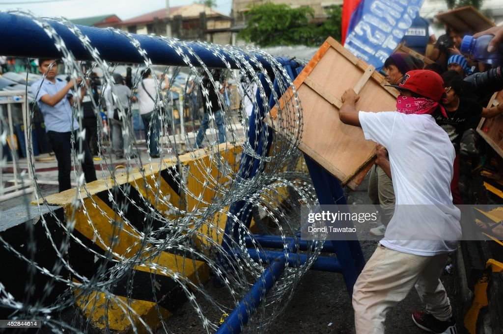 Protestors dismantle barbed wire and road blocks leading to the House of Representatives during President Benigno Aquino's annual State of the Nation Address on July 28, 2014 in Manila, Philippines. Thousands of government protestors staged a rally to protest the alleged corruption of Aquino involving the Disbursement Allocation Programme, a 145-billion-peso ($3.34-billion) fund to boost public spending but some of the funds went to favored allies in the Lower House of Representatives, reports say.