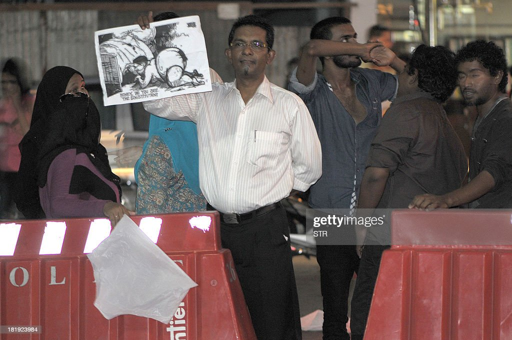Protestors display white underwear and a cartoon outside a court house in a symbol of alleged judicial corruption in suspending the September 28 run-off presidential elections in Male on September 26, 2013. Fourteen men aged between 18 and 47 were arrested after they obstructed police who tried to pull down underpants hung in front of a court house, police spokesman Hassan Haneef said. The main opposition Maldivian Democratic Party (MDP) said their supporters were raising white underpants similar to those worn by a judge during an alleged sex romp that had been secretly filmed and distributed on social media.