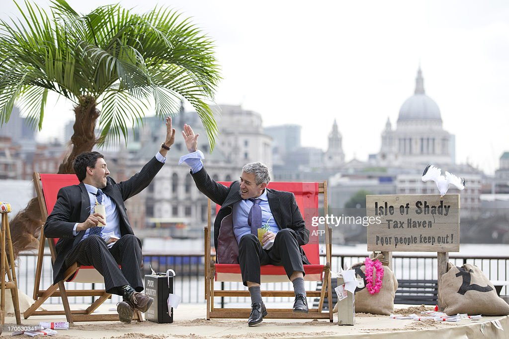 Protestors dressed as a businessman do a 'high five' on a protest site named by participants as the 'Isle of Shady Tax Haven' in London on June 14, 2013, ahead of the G8 summit as campaigners call for a crackdown on tax havens. The G8 Summit will be held in Northern Ireland on June 17 and 18, 2013. AFP PHOTO / JUSTIN TALLIS