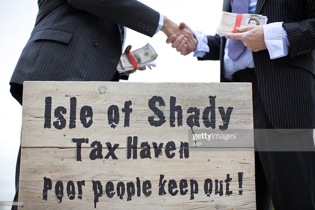 Protestors dressed as a businessman shake hands whilst holding wads of fake currency on a protest site named by participants as the 'Isle of Shady Tax Haven' in London on June 14, 2013, ahead of the G8 summit as campaigners call for a crackdown on tax havens. The G8 Summit will be held in Northern Ireland on June 17 and 18, 2013. AFP PHOTO / JUSTIN TALLIS