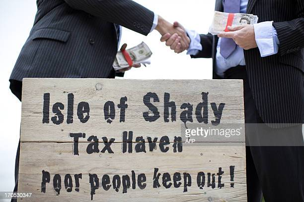 Protestors dressed as a businessman shake hands whilst holding wads of fake currency on a protest site named by participants as the 'Isle of Shady...