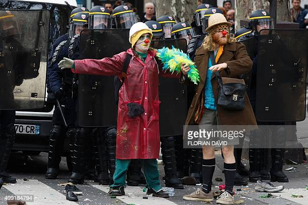 Protestors dressed as clowns stand in front of police as demonstrators clash with police during a rally against global warming on November 29 2015 in...