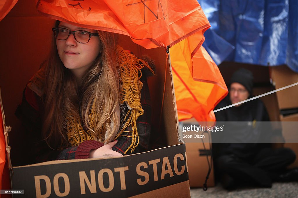 Protestors Emma LaBounty (L) and Michael Lemke sit in shanties constructed of cardboard in the Federal Building Plaza on December 6, 2012 in Chicago, Illinois. Protestors built the shantytown, which they dubbed 'Durbinville' after U.S. Senator Dick Durbin (D-IL), to persuade Durbin to push for an increase of taxes on the wealthy and oppose cuts in Social Security, Medicare, and Medicaid