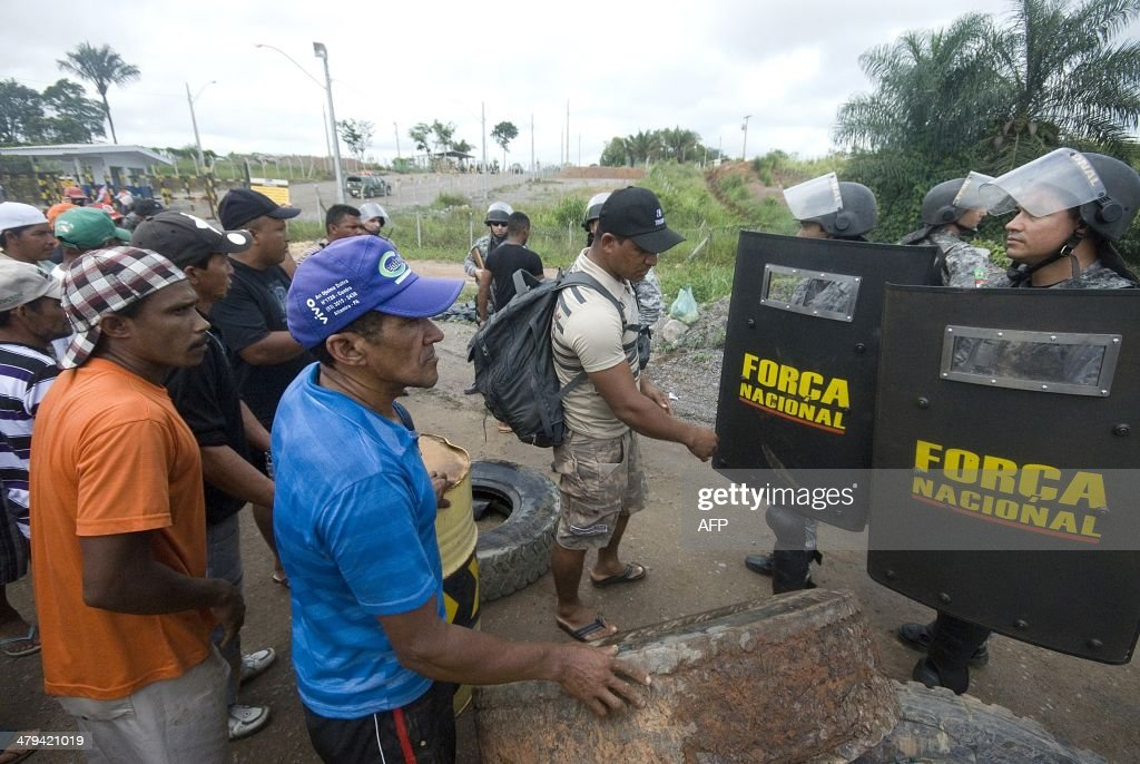Protestors face police officers during a demonstration against Norte Energia - the company responsible for the construction of Belo Monte hydroelectric power plant - demanding compensation for the loss of income from the flooding of the Xingu river near Altamira, in the northern state of Para, Brazil, on March 18, 2014. The dam will be the largest hydroelectric power plant in Brazil and provide 11% of the nation's electricity. Norte Energia says about 502km2 will be flooded and 117 social, economic and environmental projects are underway for the millions affected in the region.