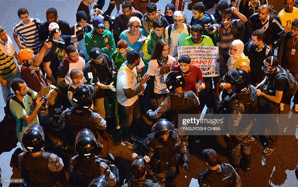 Protestors face riot squad officers on a street near Maracana stadium in Rio de Janeiro, Brazil on June 30, 2013, a few hours before the final of the FIFA Confederations Cup football tournament between Brazil and Spain. More than 11,000 police and troops were mobilised in the city to guarantee security for 78,000 fans at the venue as the curtain falls on a competition that has been beset by social unrest with more than 1.5 million people taking to the streets across the giant nation in the past two weeks. AFP PHOTO / YASUYOSHI CHIBA