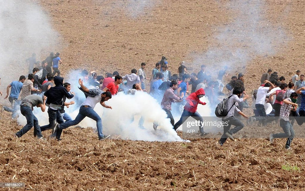 Protestors flee as tear gas explodes in a field during a demonstration near Dicle University, in Diyarbakir, on April 9, 2013. Leftist Kurdish students protest after clashes between left and right-wing groups inside Dicle University.