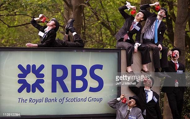 Protestors from the UK Tar Sands Network 'drink' from oil cans as they demonstrate against the RBS backing the controversial extraction of oil from...