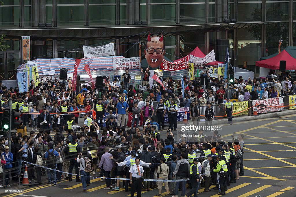 Protestors gather outside the Cheung Kong Center during a Labor Day march in Hong Kong, China, on Wednesday, May 1, 2013. Thousands of Hong Kong residents took to the streets today for Labor Day marches to petition for better labor conditions and in support of strike action by workers at docks operated by Li. Photographer: Jerome Favre/Bloomberg via Getty Images