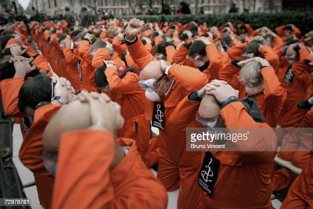 Protestors gather with their hands on their heads in front of the American embassy in London as part of an Amnesty International demonstration on...