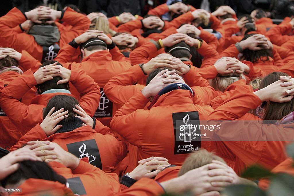Protestors gather with their hands on their heads in front of the American embassy in London as part of an Amnesty International demonstration on January 11, 2007 in London, England. The protest was organised to mark the fifth anniversary of Guantanamo detention center, Camp X-ray opening on the US naval base in Cuba. Human rights groups continue to argue that the detainees should be either charged or released.
